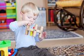 Little Toddler Boy Playing With Wooden Toys