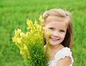 Smiling Cute Little Girl With Flowers On The Meadow