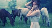 Beautiful woman among horses