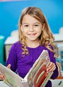 Portrait of cute girl smiling while holding book in kindergarten