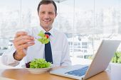 Smiling businessman eating a salad during the lunch time