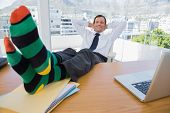 Smiling businessman having a nap with feet over a pile of documents on the desk