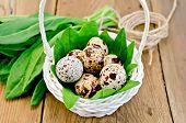 Huevos de codorniz en una cesta blanca con acedera en el tablero