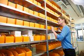 Female Pharmacy Worker Looking At Shelves For Drugs And Medicine