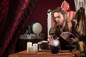 stock photo of seer  - Male fortune teller concentrating on his crystal ball - JPG