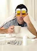 pic of hangover  - exhausted young Man in bed with coffee water and tablets suffering hangover and headache - JPG