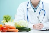 picture of scrubs  - Nutritionist Doctor is writing a diet plan - JPG