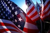 stock photo of waving american flag  - In the middle of a bunch of American flags on a clear day - JPG