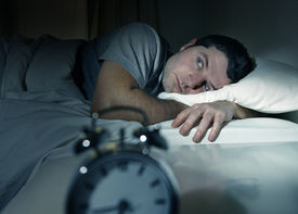 stock photo of suffering  - young man in bed with eyes opened suffering insomnia and sleep disorder thinking about his problem - JPG