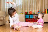 Mom And Kid Doing Exercises Sitting On The Floor In Home Interior