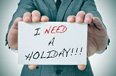 businessman showing a signboard with the text I need a holiday written in it