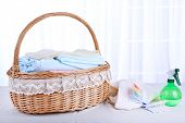 Colorful towels in basket on table, on light background