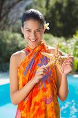 Smiling brunette in sarong showing starfish to camera outside at the spa