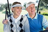 picture of buggy  - Happy golfing couple sitting in golf buggy smiling on a sunny day at the golf course - JPG