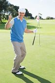 Happy golfer cheering on putting green at eighteenth hole on a sunny day at the golf course