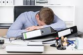 Young Exhausted Man Is Lying On The Desk In Office
