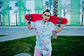 Attractive teenager with bright clothes standing with skateboard