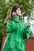 stock photo of dreads  - Cool girl with dreads walking and listening music