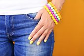 Female hand with stylish colorful nails, close-up, on color background