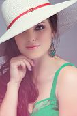 Portrait of a beautiful young brunette woman. Wearing white hat over long loose curly hair. Open shoulders summer emerald green dress. Against pink vintage studio background.