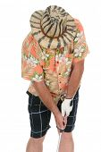 Closeup of an eclecticly dressed male tourist standing over a golf ball preparing to take his turn.