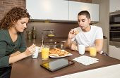 Serious and bored couple having a home breakfast