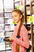 Girl holds tablet near bookshelf in library