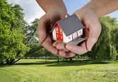 stock photo of nice house  - Hand with a house over a nice building plot.