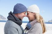 Attractive couple smiling at each other on the beach in warm clothing on a bright but cool day