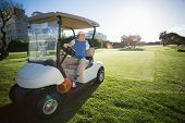 Golfer reversing his golf buggy on a sunny day at the golf course