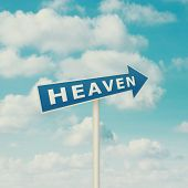Road sign pointing to heaven, blue sky with clouds as background in vintage retro style.
