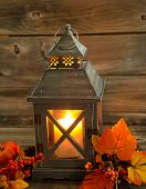 Traditional Asian Lantern Glowing Brightly With Autumn Decorations On Rustic Wood