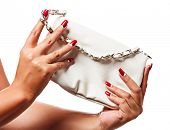 closeup of the woman's hand wearing red half moon nail art manicure with white leather bag with silv