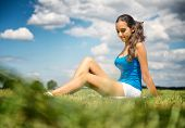 Beautiful slender tanned leggy young girl in shorts sitting relaxing in a green field in the warm su