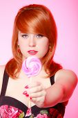 Young Woman Showing Candy. Redhair Girl Giving Sweet Lollipop