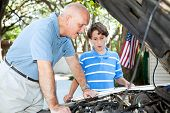 Father teaching his son how to do auto repair.