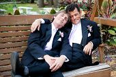 Gay couple relaxes on a swing after their marriage ceremony.