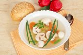 Plate with soup, spoon, bread and red tulips