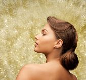 beauty, holidays, people and hairstyle concept - beautiful young woman with bare shoulders over golden lights background
