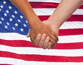 friendship, patriotism, gesture and people concept - closeup of two hands hands holding over american flag