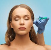 medicine, plastic surgery, beauty, health and people concept - hand in medical glove with syringe making injection to beautiful woman face over blue background
