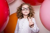 Young Girl In Glasses Showing Two Fingers Victory Against The Background Of Large Colorful Balloons