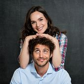 Man Looking At Happy Woman Leaning On His Head