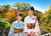 KYOTO - OCT 24,2014: Two japanese women with traditional kimono in fall park on Oct 24, 2014,Kyoto, Japan. Viewing the fall foliage is a cultural pastime in Japan dating from antiquity.