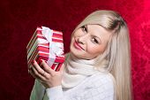 A Girl In A White Sweater And Striped Gift With White Bow Looking At The Camera.