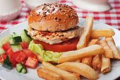 Chicken burger with lettuce, tomato and french fries