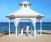 Loving couple in belvedere on the beach. Wedding.