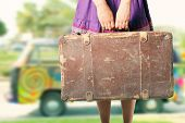 stock photo of road trip  - hippie girl with old suitcase on a road trip - JPG
