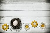 Egg in nest with flowers around on wooden background -Concept that announces spring and Easter holidays