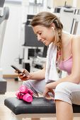 Smiling Woman With Smartphone At The Gym